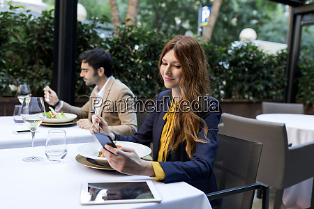 man eating and woman using cell