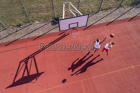 two young men playing basketball on
