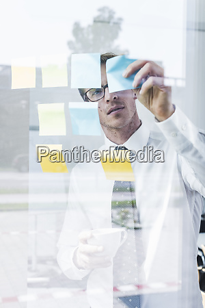 businessman attaching adhesive notes at glass