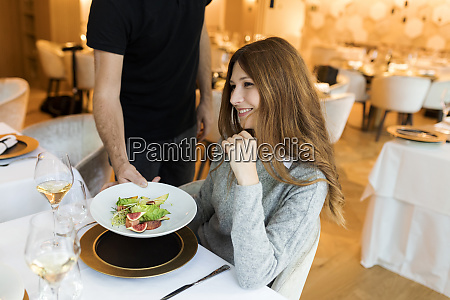 waiter serving dish for smiling woman