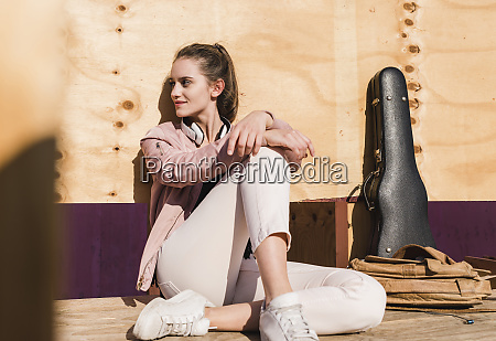 relaxed young woman sitting on platform