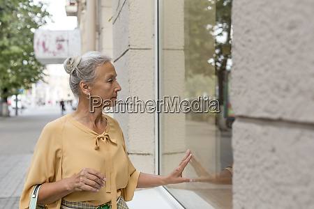 senior woman looking in shop window