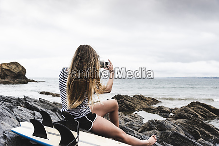 young woman with surfboard sitting on