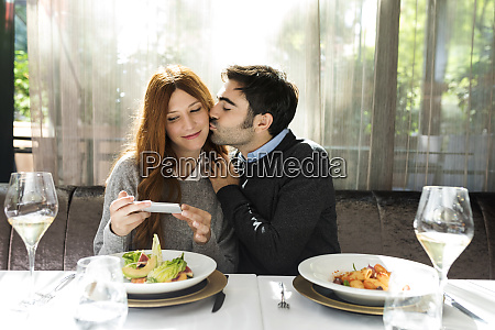 man kissing woman taking a cell