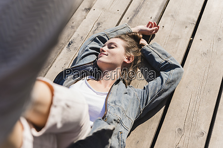 relaxed young woman lying on wooden