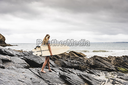 young woman carrying surfboard on a