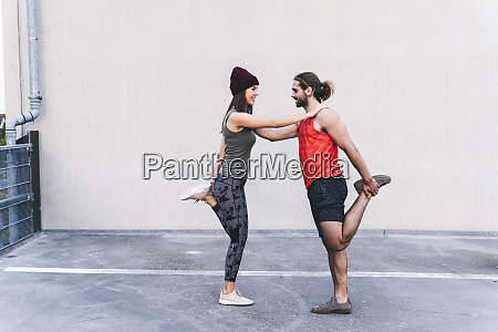 fit young couple doing partner exercises