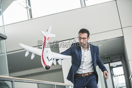 businessman playing with toy aeroplane in