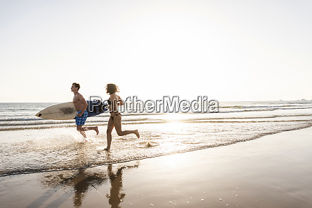 young couple running on beach carrying