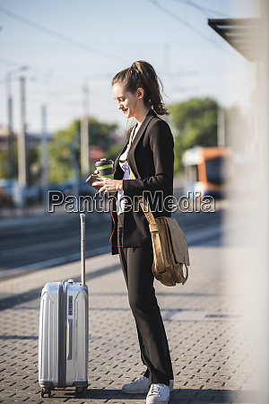 young woman with luggage at tram