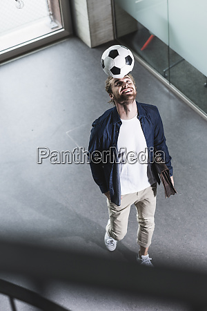casual young businessman playing football in