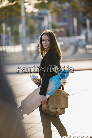 young woman with longboard in the
