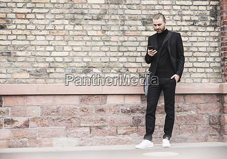 young man standing at brick wall