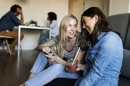 two cheerful young women sitting on