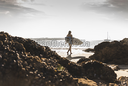 france brittany young woman carrying surfboard