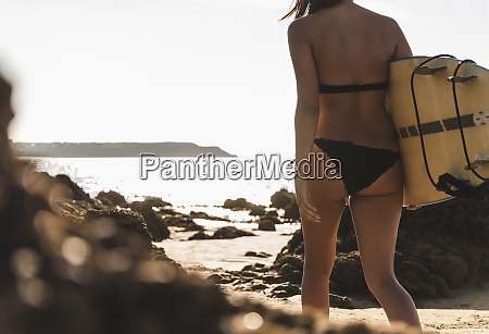 france, , brittany, , young, woman, carrying, surfboard - 26403240