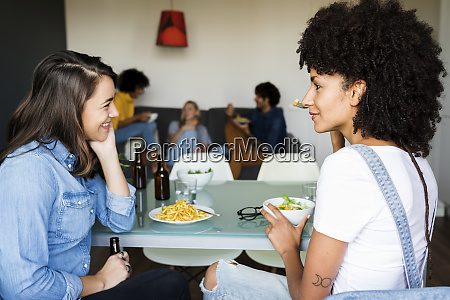 girlfriends sitting at dining table with