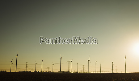 wind turbines against sunny sunset sky