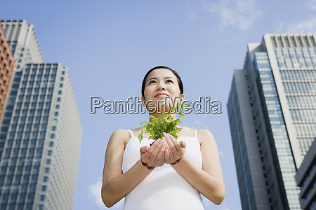 portrait young woman holding green sapling