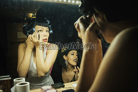female burlesque performers getting ready applying