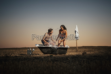 playful couple splashing in bathtub in