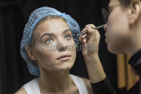 makeup artist applying makeup to eyes
