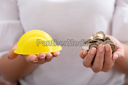 person holding hardhat and golden coins