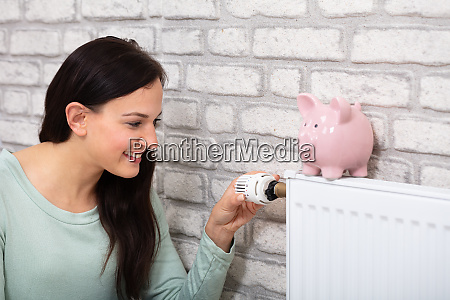 woman adjusting thermostat with piggy bank