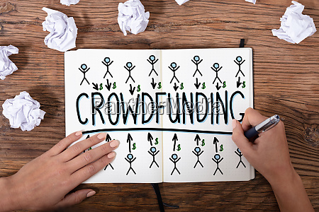businesswomans hand drawing crowdfunding concept
