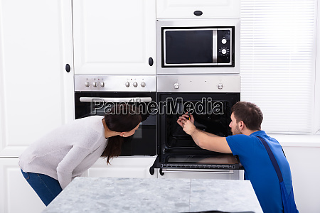 technician in overall fixing oven in