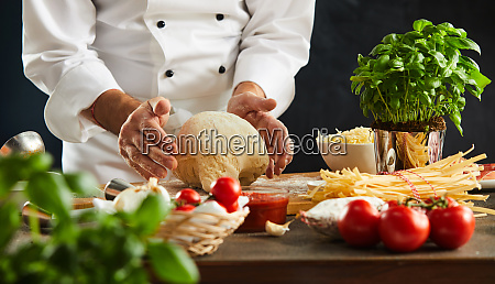 chef preparing dough for a pizza