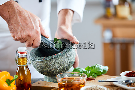 chef crushing a blending fresh herbs
