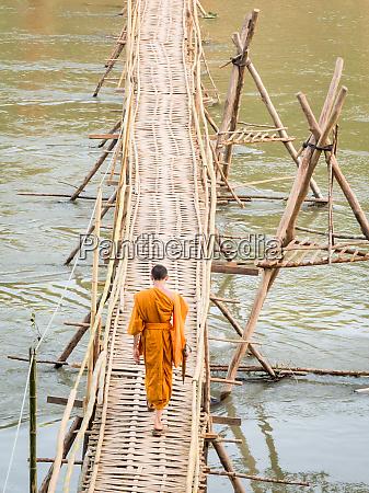 orange clad buddhist monk crossing a