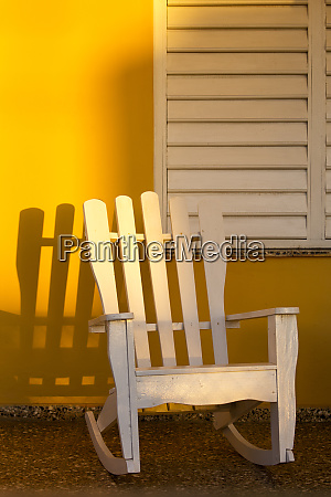 white rocking chair on yellow porch