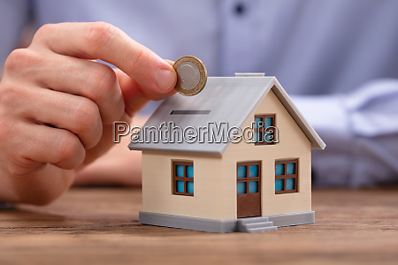 person inserting coin in house piggybank