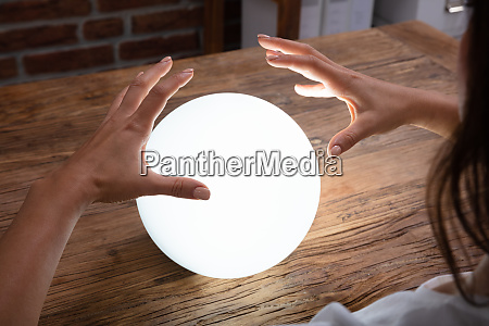 fortunetellers hand covering the crystal ball