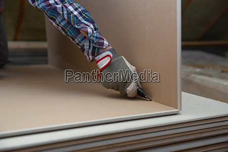 worker cutting drywall plasterboard with construction