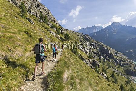 hikers on path towards rifugio bignami
