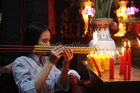 vietnamese woman praying with incense sticks