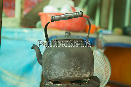 old teapot in soot boil water