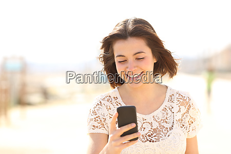 woman walking checking phone content in
