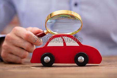 person looking red car through magnifying