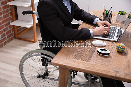 businessman sitting on wheelchair using laptop