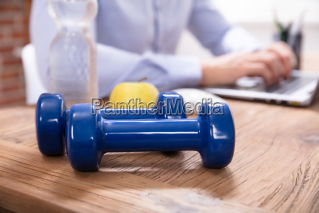 water bottle and blue dumbbells on