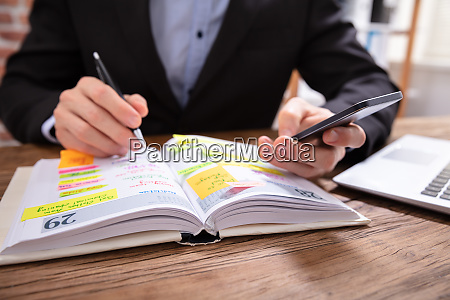businessman holding cellphone writing schedule in