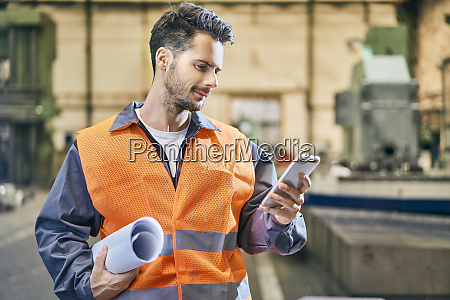 smiling man holding blueprints and looking