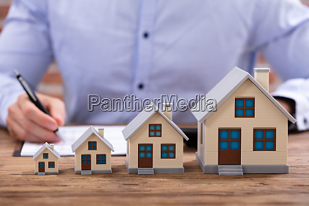 businessman calculating invoice with house model