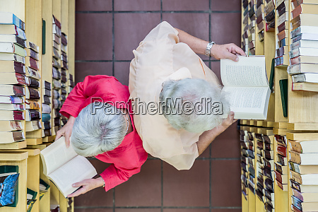 two users reading books back to