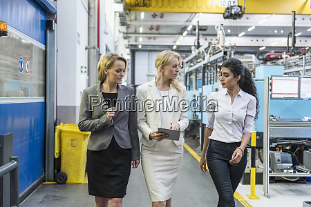 three women with tablet walking and