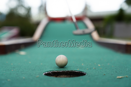 ball and club playing miniature golf